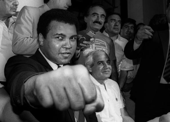A smiling Muhammad Ali shows his fist to reporters during an impromptu press conference in Mexico City. REUTERS/Jorge Nunez