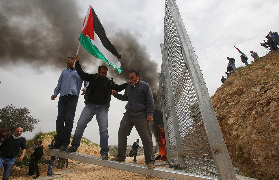 Палестинские демонстранты пытаются сломать забор, установленный израильтянами, во время акции протеста на Западном берегу реки Иордан в городе Бейт-Джала.