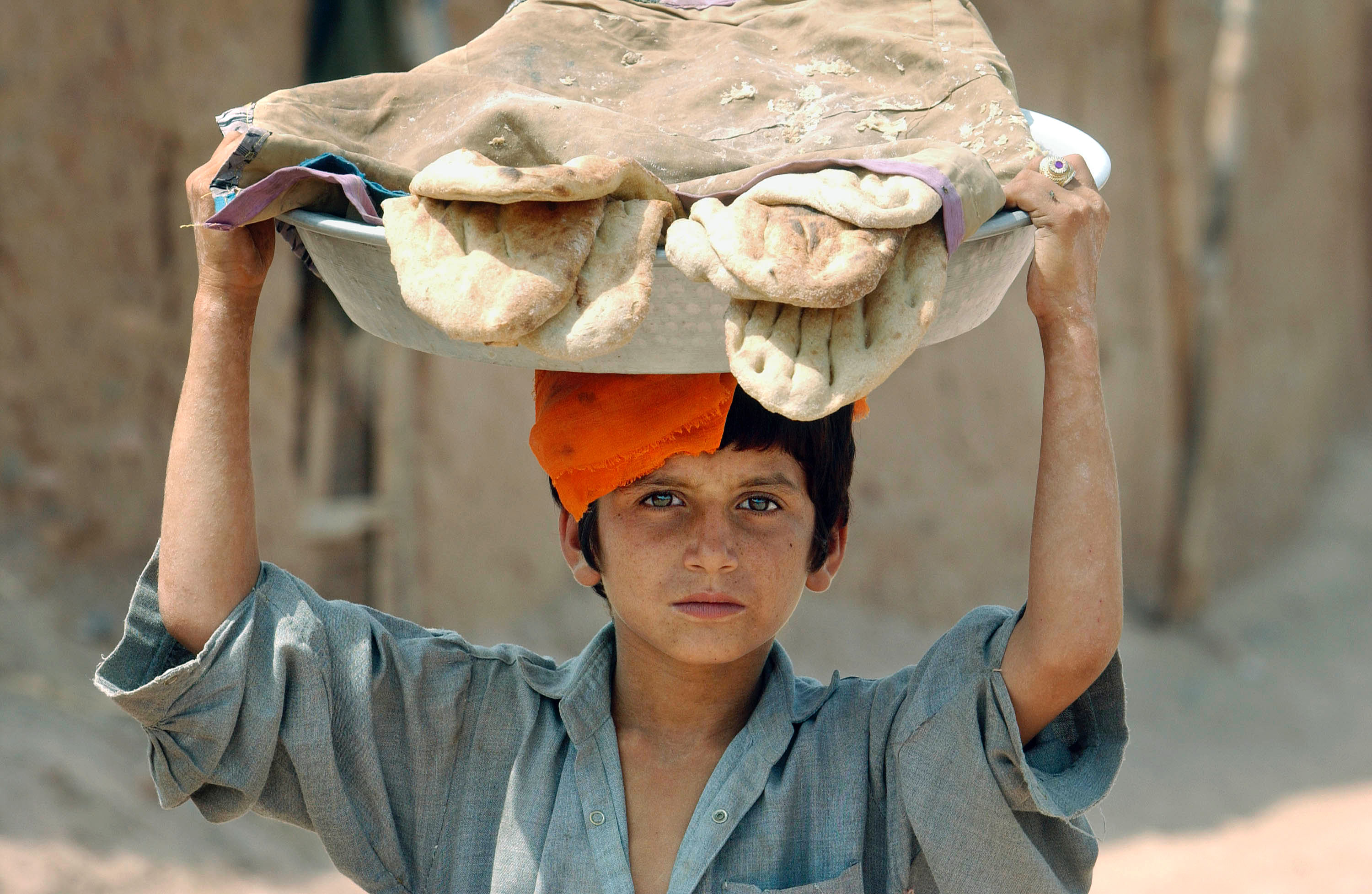 SHAMSHATU REFUGEE CAMP, PAKISTAN - AUGUST 30:  An unidentified Afghan refugee child carries a platter of nan bread through the deserted dirt streets of the Shamshatu refugee camp August 30, 2002 in Pakistan near the border of Afghanistan. To the surprise of many observers, hundreds of thousands of Afghani refugees in Pakistan have flooded back into their home country since January, some after 20 years of exile. Tens of thousands have left the once-crowded Shamshatu camp alone, leaving large areas of it deserted.  (Photo by Chris Hondros/Getty Images)