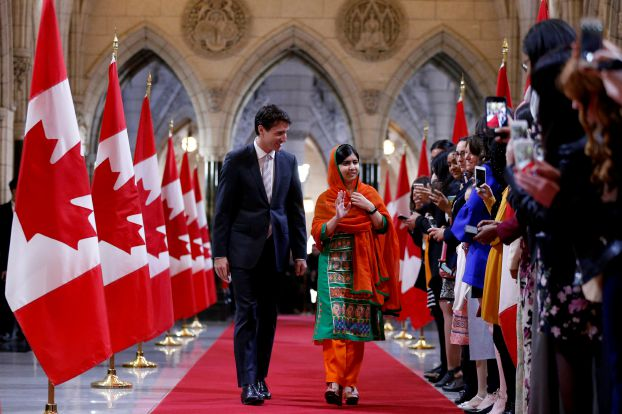 Canada's Prime Minister Justin Trudeau (L) walks with Pakistani Nobel Peace Prize laureate Malala Yousafzai in the Hall of Honour on Parliament Hill in Ottawa, Ontario, Canada, April 12, 2017. REUTERS/Chris Wattie