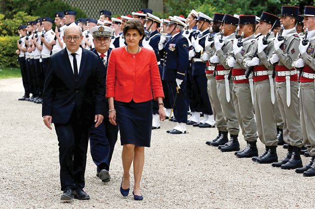 Jean-Yves Le Drian (L), outgoing French defence minister, and newly-appointed Foreign Minister and Minister for Europe, reviews the troops with Sylvie Goulard, newly-appointed Defence Minister, as they attend a handover ceremony at the Defence Ministry in Paris, France, May 17, 2017.  REUTERS/Gonzalo Fuentes