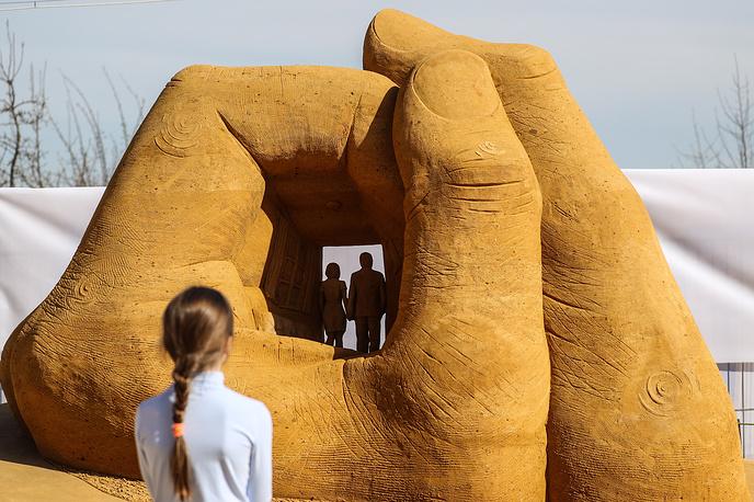 """MOSCOW, RUSSIA - APRIL 29, 2017: A sand hand on display during the World Championship of Sand Sculpting at the Kolomenskoye historical and nature reserve museum. Sergei Savostyanov/TASS  Ðîññèÿ. Ìîñêâà. 29.04.2017. Ïîñåòèòåëè ó ñêóëüïòóðû """"Ìû"""", ïðåäñòàâëåííîé íà ÷åìïèîíàòå ìèðà ïî ñêóëüïòóðå èç ïåñêà â ìóçåå-çàïîâåäíèêå """"Êîëîìåíñêîå"""". Ñåðãåé Ñàâîñòüÿíîâ/ÒÀÑÑ"""