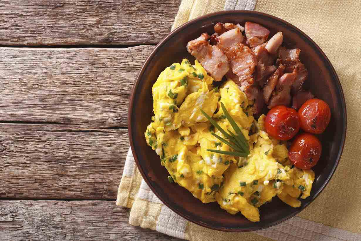 Breakfast Is Scrambled Eggs With Chives, Fried Bacon Closeup. Ho
