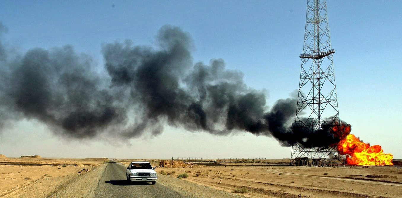 A car passes along a highway as fire rages at a strategic oil pipeline near the town of Hit, 140kms north of Baghdad Sunday 22nd June 2003. The fire is believed to have been caused by sabatage and oil ministry officials have said it could affect production.  EPA PHOTO/DPA/VALDRIN XHEMAJ