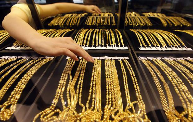 An employee arranges gold jewellery in the counter as her arm is reflected in the mirror at a gold shop in Wuhan, Hubei province August 25, 2011. The Shanghai Gold Exchange will raise margin requirements for its gold forward contracts for the second time this month to 12 percent starting on Friday, in a move aimed at curbing excessive risk-taking following the rapid rally in gold prices. REUTERS/Stringer (CHINA - Tags: BUSINESS)