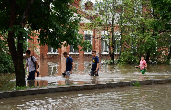 PRIMORYE TERRITORY, RUSSIA - AUGUST 7, 2017: People in a flooded street in the town of Ussuriysk as heavy rains hit the Russian Far East. Yuri Smityuk/TASS  Ðîññèÿ. Ïðèìîðñêèé êðàé. 7 àâãóñòà 2017. Æèòåëè Óññóðèéñêà íà îäíîé èç çàòîïëåííûõ óëèö ãîðîäà. íî÷ü ñ 6 íà 7 àâãóñòà 2017 ãîäà â þæíûõ ðàéîíàõ Ïðèìîðñêîãî êðàÿ âûïàëî áîëüøîå êîëè÷åñòâî îñàäêîâ. Þðèé Ñìèòþê/ÒÀÑÑ