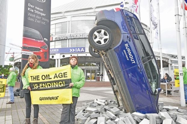 "Greenpeace activists protest against climate-damaging cars with an installation with a car set-up upright and banners reading ""the oil age is ending"" on the sidelines of the Frankfurt Motor Show IAA in Frankfurt am Main, western Germany, on September 12, 2017.  According to organisers, around 1,000 exhibitors from 39 countries will showcase their products and services. This year's fair running from September 14 to 24, 2017 will focus on digitization, urban mobility and electric mobility. / AFP / Tobias SCHWARZ"