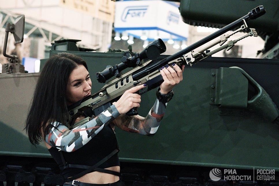 """Девушка осматривает винтовку на выставке """"Оружие и безопасность"""" в Киеве."""