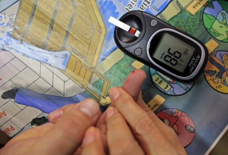 عاملة في مجال الصحة توضح طريقة قياس مستوى السكر في الدم في المركز القومي للسكر والتغذية وأمراض الأيض في رومانيا. أرشيف رويترز